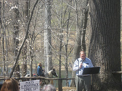 Peter Krok reads as a cowboy passes in the background