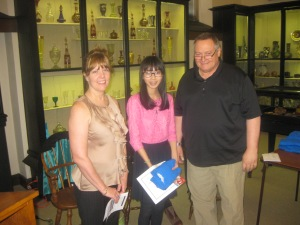 Melissa Phung receives her award, certificate and shirt from Diane Sahms-Guarnieri and Gary Martinez