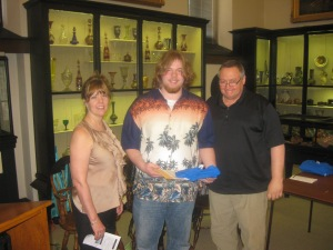 Drew Schmidt receives his award, certificate and shirt from Diane Sahms-Guarnieri and Gary Martinez