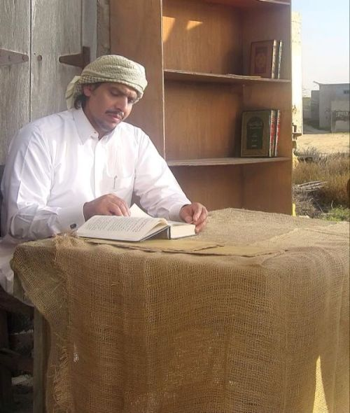 Mohammed Al Ajami reading at table pic